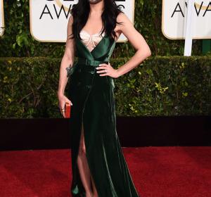 Conchita Wurst con un vestido verde de terciopelo y zapatos acabados en punta